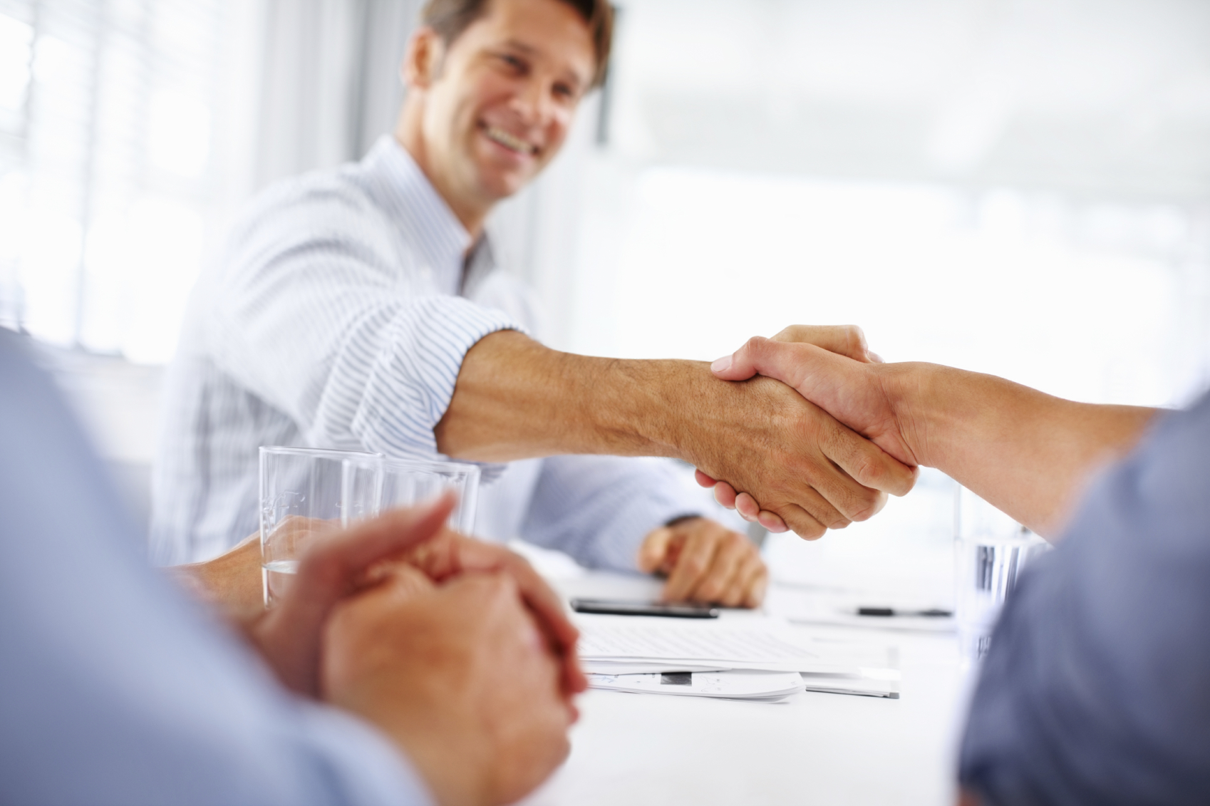Portrait of business man shaking hands with colleague in meeting